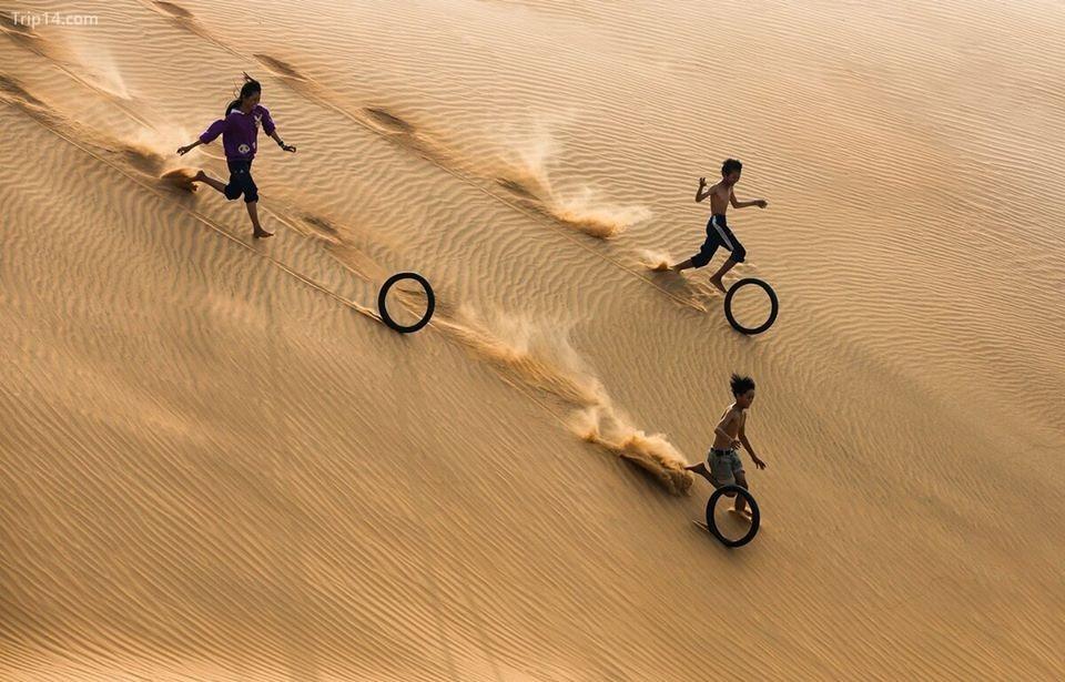 """Tác phẩm """"Trò chơi đơn giản"""" của tác giả Trần Tuấn Việt, ghi lại hình ảnh nhóm trẻ em đang chơi với những chiếc lốp xe máy cũ trên cồn cát Mũi Né, Phan Thiết, Bình Thuận"""