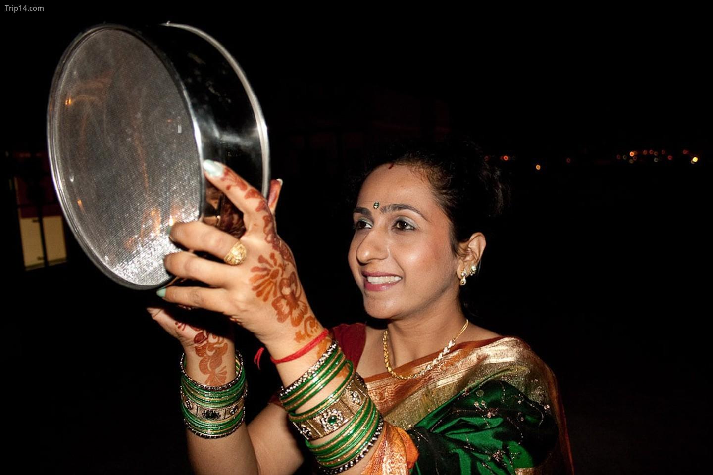 Một phụ nữ Hindu đã kết hôn nhìn mặt trăng qua sàng trên Karva Chauth   |
